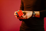 man holding Rubik's cube and playing with it . On red background