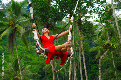 Foto auf Gartenposter Grun attractive happy middle aged 40s or 50s Asian Indonesian woman with grey hair riding rainforest swing carefree swinging and enjoying tropical jungle adventure