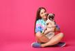 Leinwandbild Motiv Teenage girl with cute pug dog on color background