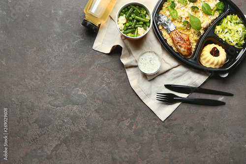 Container with delicious food and drink on grey background