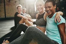 Two Smiling Women Sitting In A Gym After Working Out