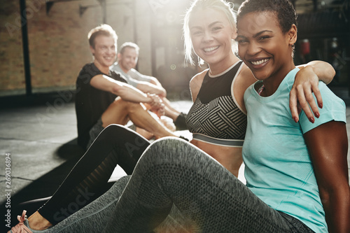 Papiers peints Fitness Two smiling women sitting in a gym after working out