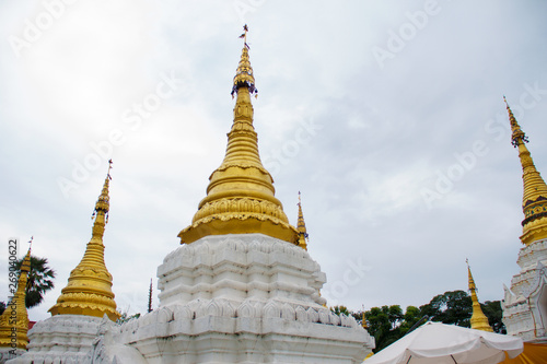 In de dag Bedehuis Many golden pagodas on the courtyard of temple in northern thailand, with blue sky background.