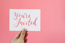 """Hand Holding Card With Text """"You're Invited"""""""
