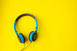 canvas print picture - Blue headphones on yellow background.concept of entertainment
