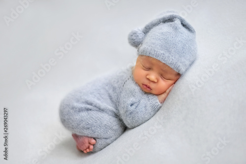 Fototapeta Sleeping newborn boy in the first days of life on white background obraz na płótnie