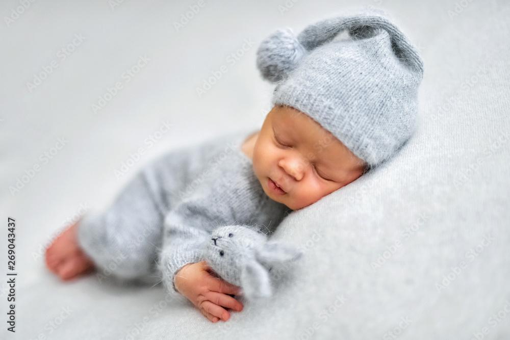 Fototapeta Sleeping newborn boy in the first days of life on white background - obraz na płótnie