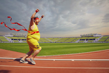 Fat Funny Man Runs To The Finish On Track In The Stadium.
