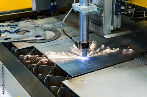 Automatic CNC plasma cutting machine cuts details from steel sheet.