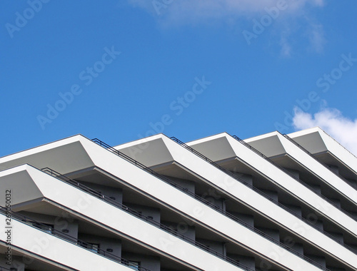 corner details of a geometric white modern apartment block diagonal geometric balconies and railings against a bright blue sky Wall mural