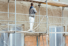 Worker Plastering Outer Wall O...
