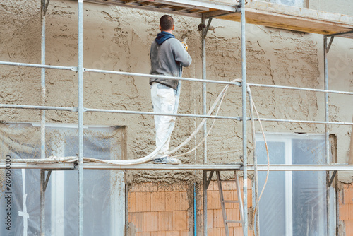 Fototapeta Worker plastering outer wall of newly built house obraz