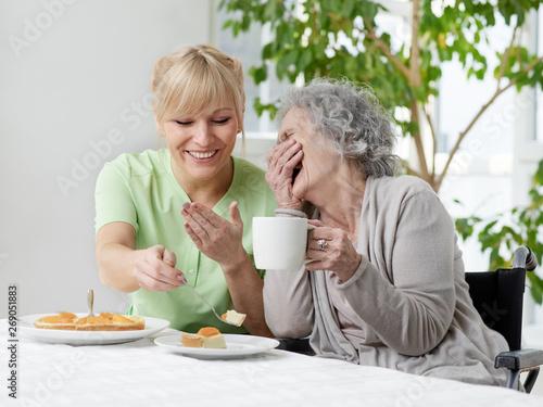 Papel de parede Seniorin und Pflegerin haben Spass beim Kaffee