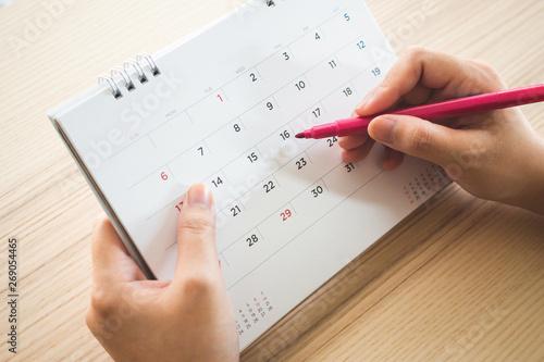 Obraz Hand with pen writing on calendar page closeup - fototapety do salonu