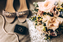Wedding Accessories On A Pillow With Sequins: Two Silver Wedding Rings, Bridal Bouquet, Shoes And Beads With Pearls. Romantic Greeting Card, Engagement, Celebration, Invitation, Love. Photos In