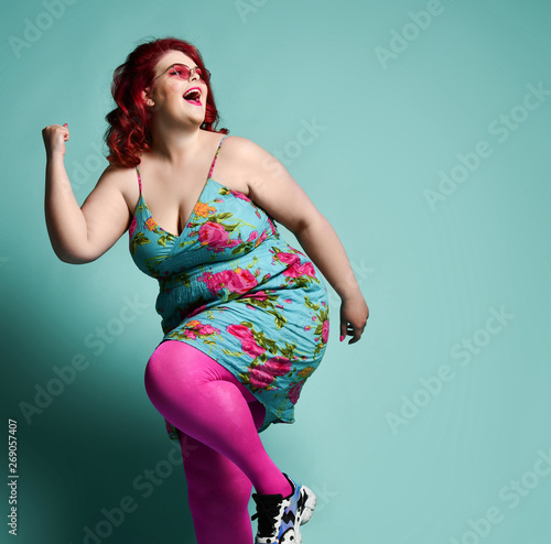 Laughing plus-size lady overweight woman in fashion sunglasses and sundress running from something on mint with text copy space Wall mural