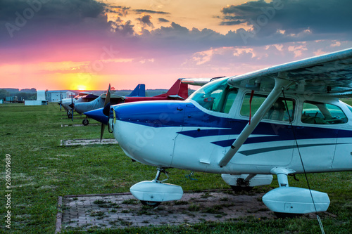Photo Small private aircrafts parked at the airfield at picturesque sunset