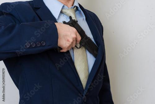Fényképezés  Business man in suit holding hand gun on white background