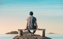 A Man Is Sitting On A Wooden Bench. He Looks At The Sea. Back View
