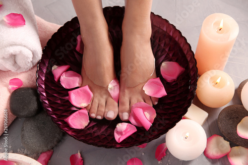 Woman soaking her feet in bowl with water and rose petals on grey floor, top view. Spa treatment