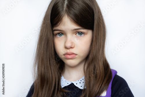 Photo portrait of a sad crying girl in school uniform, closeup on white background