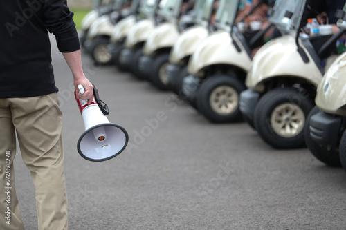 Canvas Print A gentleman holds a megaphone just prior to briefing golfer participating in a golf outing
