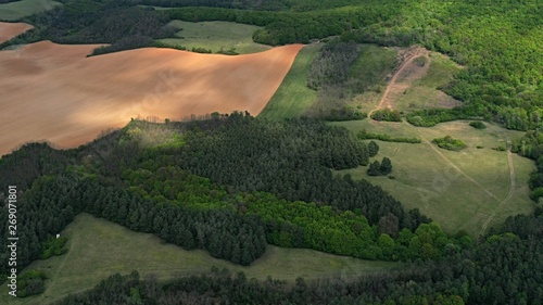 Fotografia, Obraz  Aerial view of lowlands in western Slovakia, with fields, grassland, meadows and patches of light shining through clouds