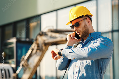 Construction engineer talking on the phone and looking at the watch on the construction site