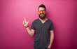 canvas print picture - Cheerful bearded man pointing up with finger, over pink background