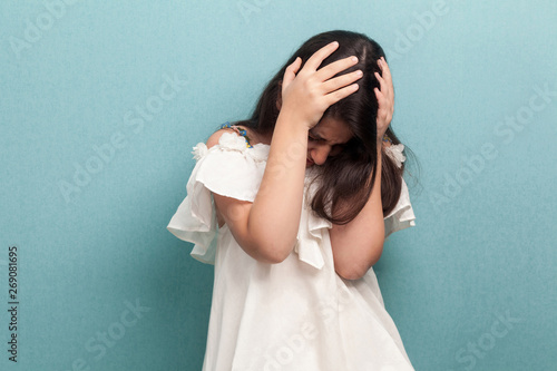 Fotografie, Tablou  Portrait of sad beautiful brunette young girl with black long straight hair in white dress standing holding her head down and depressed