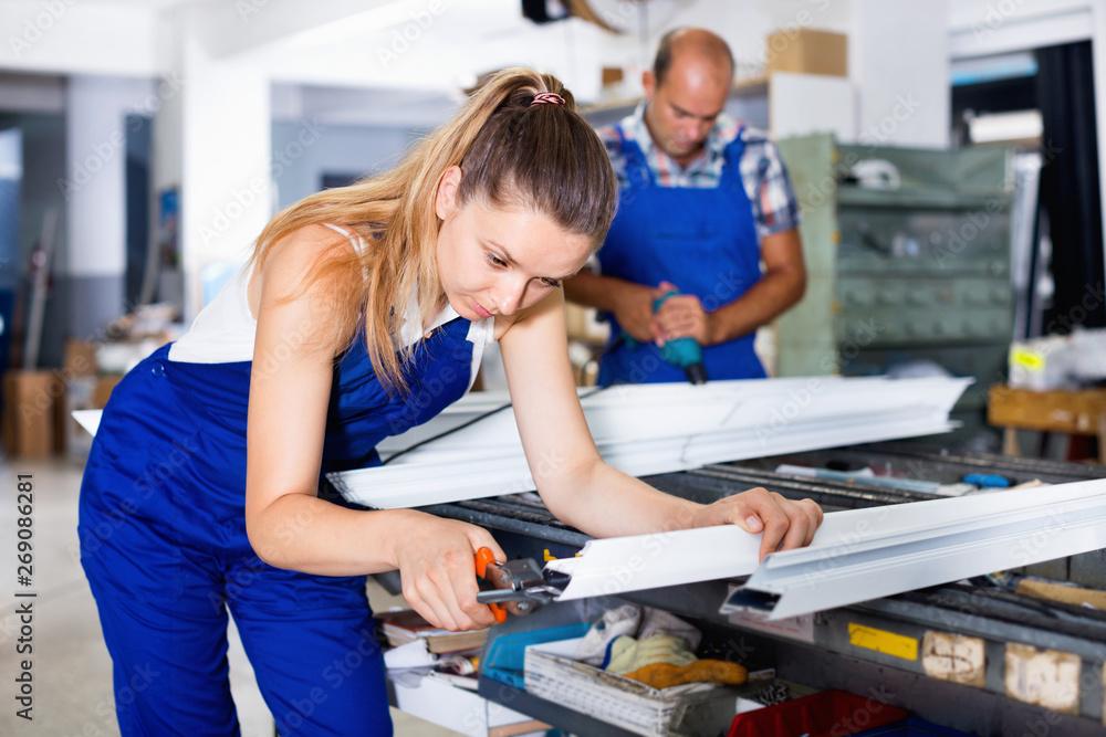 Leinwandbild Motiv - JackF : Female worker cutting metal-plastic profiles in workshop, using nippers