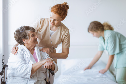 Fotografie, Obraz Elderly woman on wheelchair in nursing home with helpful doctor at her side and