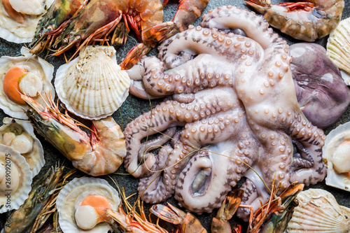 Assortment of seafood with raw fresh octopus, scallops and prawns, as an gourmet dinner background