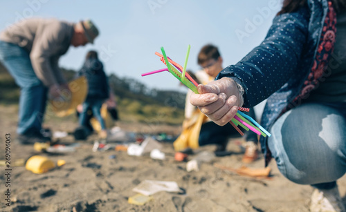 Photo Woman hand showing handful of straws collected on the beach with group of volunteers working in the background