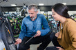positive man reviewing bicycles at bike store