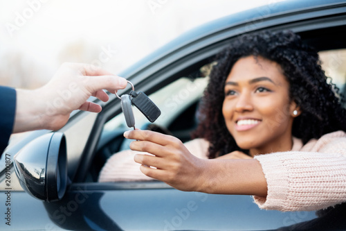 Portrait of young black woman sitting in car