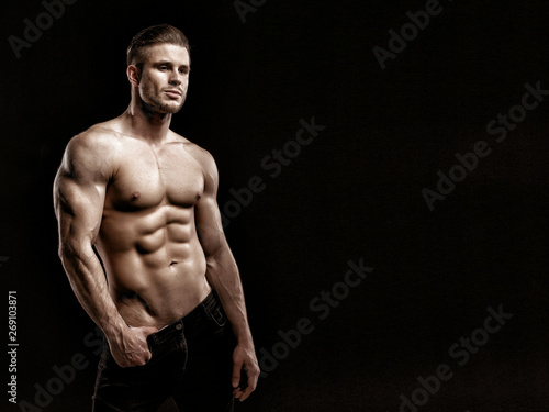Fotografie, Tablou  Muscular model young man on dark background