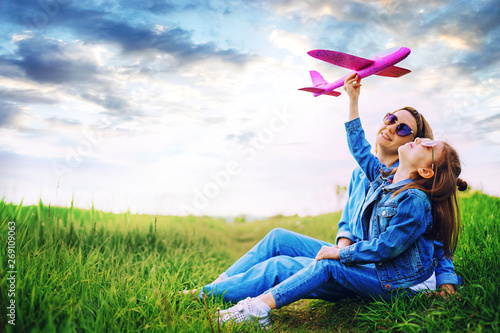 Side view of little girl in denim outfit playing with pink plane while sitting on green grass near mother against cloudy sky in nature