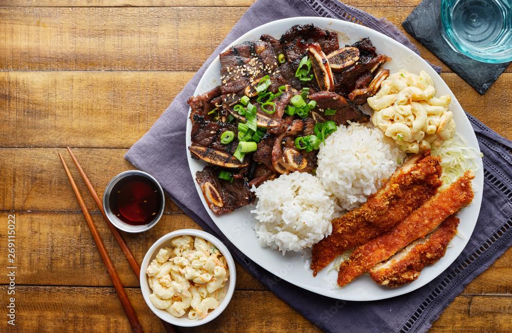 Fototapeta hawaiian bbq plate with mix of chicken katsu, korean kalbi beef short ribs, rice, and macaroni salad overhead composition