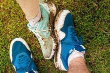 Dirty Sneakers On Two People's Feet With Grass In The Background. Dirty New Shoes. Concept Of Bad Day.