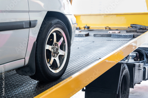 Fotografie, Obraz  Closeup on car towed onto flatbed tow truck with cable