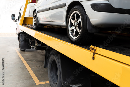 Broken car on flatbed tow truck being transported for repair Fototapet