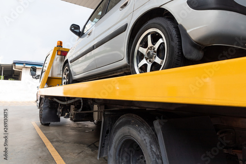 Broken car on flatbed tow truck being transported for repair Canvas Print