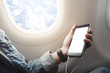 Asian man touching and slide mobile phone screen on airplane or aircraft,blank mobile phone screen mock up,selective focus