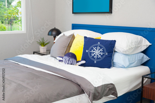 Fototapety, obrazy: blue and yellow pillow on teen's bedroom with vase and picture frame.