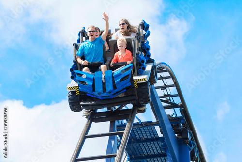 Fotografia Young family having fun riding a rollercoaster at a theme park