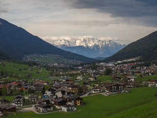 Fototapeta na wymiar Spring mountain rural landscape. View over Stubaital Stubai Valley near Innsbruck, Austria with village Neder, green meadow, forest, snow covered alpen mountain peaks, evening dramatic clouds and