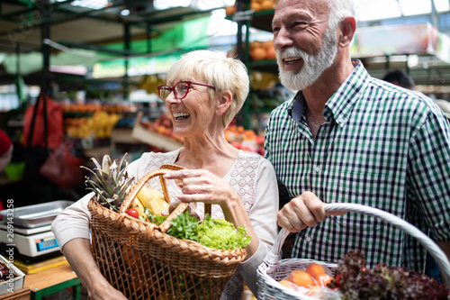 Shopping, food, sale, consumerism and people concept - happy senior couple buying fresh food - 269143258