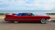 Classic Red 1950's 4 Door Cadillac  Motor Car Parked On Seafront Promenade.