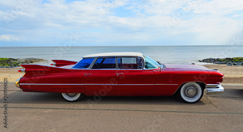 Fotografia, Obraz Classic Red 1950's 4 door Cadillac  motor car parked on seafront promenade